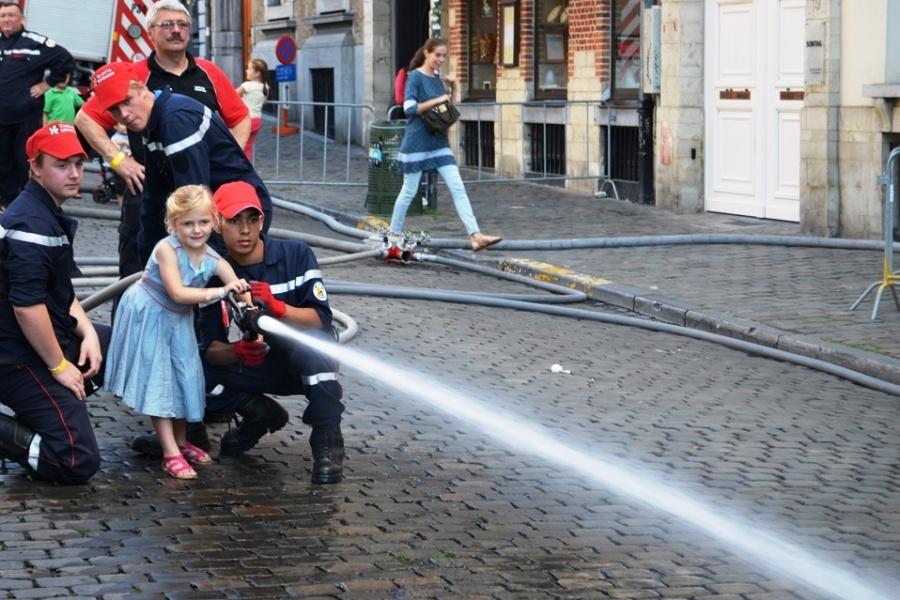 De jeugdbrandweer leert kinderen hoe ze een brandslang moeten vasthouden